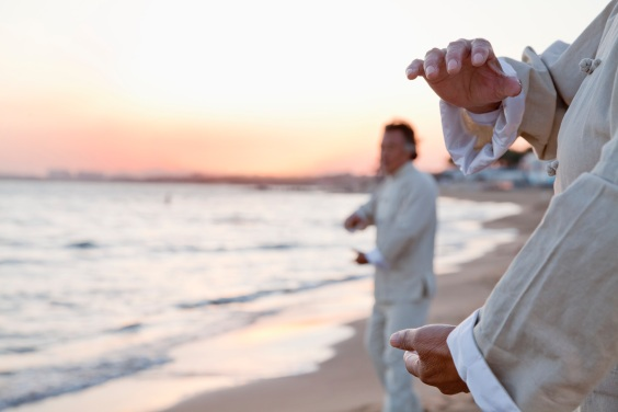 Two older people practicing Taijiquan on the beach at sunset
